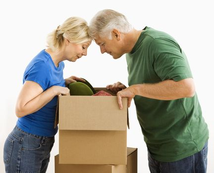 Middle-aged couple looking through cardboard box.