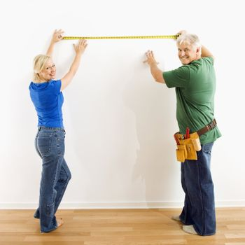 Middle-aged couple measuring wall with tape.