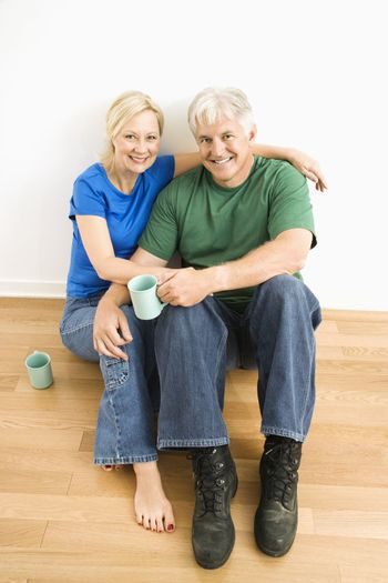 Middle-aged couple sitting on floor together drinking coffee.