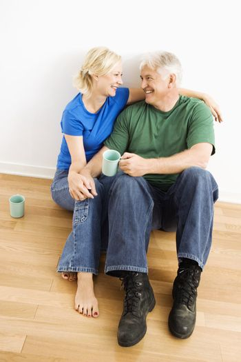 Middle-aged couple sitting on floor snuggling and drinking coffee.