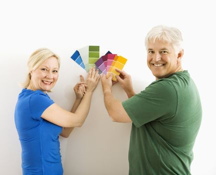 Middle-aged couple holding up and comparing paint swatches.