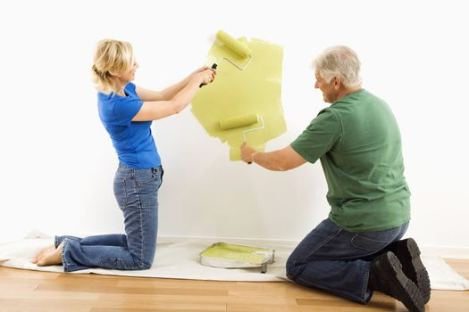 Middle-aged couple beginning to paint wall green over drop cloth.