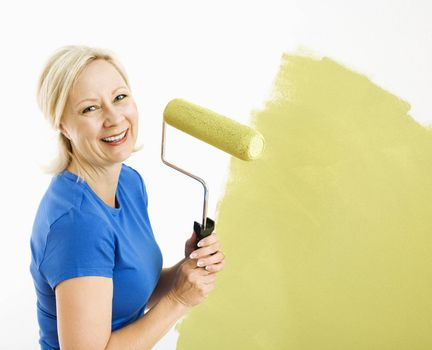 Middle-aged woman painting wall green with paint roller smiling at viewer.