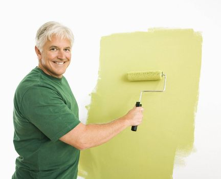 Middle-aged man painting wall green with paint roller smiling at viewer.