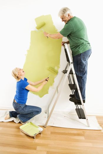 Middle-aged couple painting wall green with male on ladder.