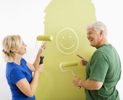 Middle-aged couple painting wall green finger-painting smiley face for fun.