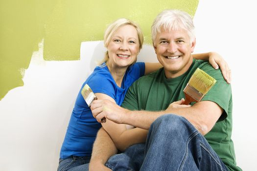 Middle-aged couple snuggling in front of wall they are painting green.