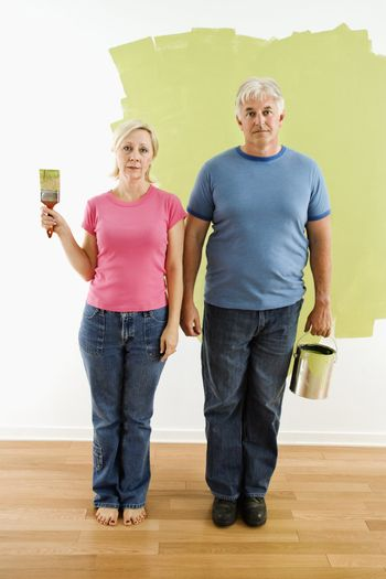 "Portrait of unhappy adult couple standing in front of half-painted wall with paint supplies ""American Gothic"" style."