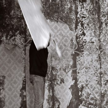 Obscured figure in empty room with torn wallpaper. Motion blur, black and white.