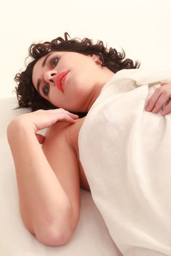 Young woman lying nude in bed dreaming