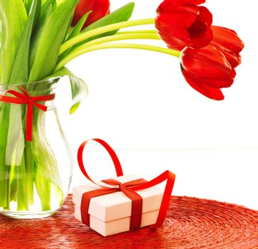 Closeup photo of beautiful romantic still life isolated on white background, fresh red tulips bouquet, small white present with ribbon decoration, happy mothers day, love and romance concept
