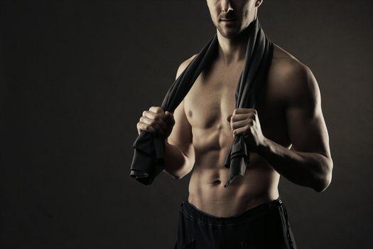 Muscular, shirtless man with towel around neck