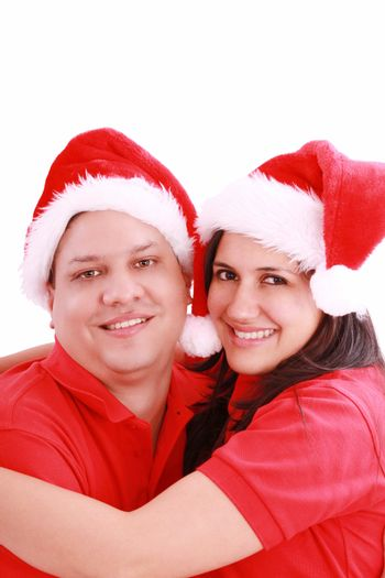 Young happy couple near with Santa hats. Isolated over white background