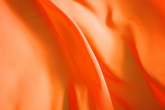 orange fabric winds waves, creating a beautiful background of the folds