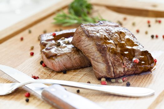 Two Tasty Steaks On a Wooden Board
