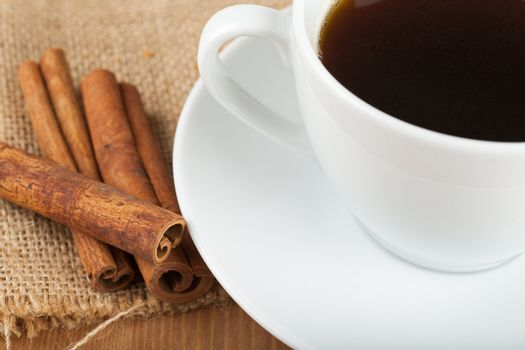 Cup of coffee and cinnamon on a wooden table