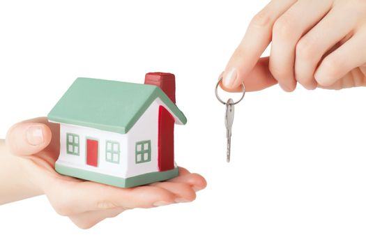 Little house toy and key in hands isolated over white background