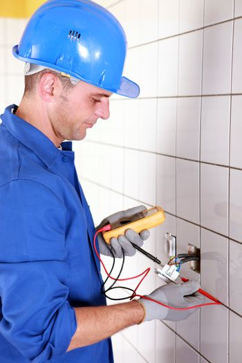 Plumber checking wiring with a voltmeter