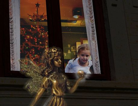 Little girl looking out of the window on Christmas Eve, seeing a glittering fairy holding a glowing apple.