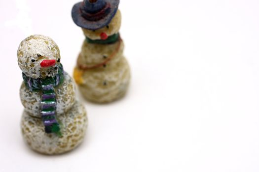A couple of wooden snowmen on white background