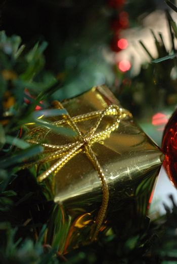 Close up of small golden Christmas decoration in the shape of a parcel. against dark green of Christmas tree.