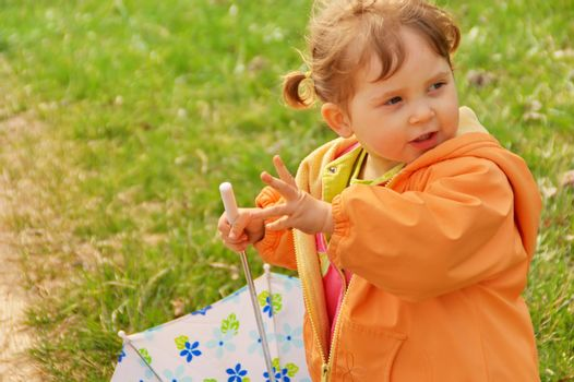 Little girl playing with umbrella at park. Green grass  background. Spring time.