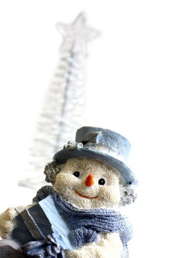 Shot of Snowman figurine with a christmas tree in the background