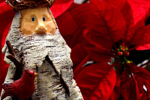 Wooden Statue of Santa Claus with Poinsettia backdrop