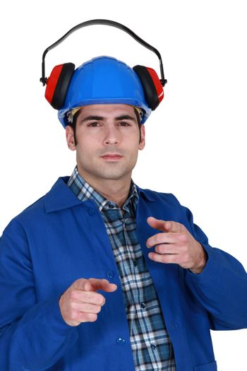 portrait of helmeted craftsman with earmuffs showing off