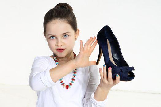 Little fashionista holding shoe in studio