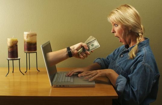 Attractive business woman shocked to see a hand coming through her laptop screen handing her lots of money. Can it be that simple?