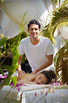 Masseur at work massaging woman in luxury spa
