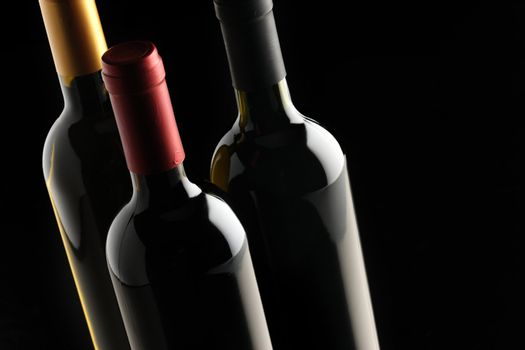 bottles of red and white wine on black background