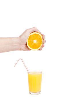 hand pour orange juice from orange