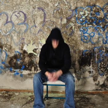 Blurry male figure sitting against dirty wall covered with black mold and messy paint.