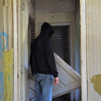 Unhinged door in the doorway of an abandoned house and hooded figure.