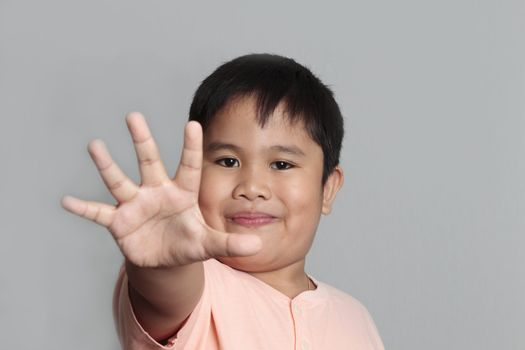 Child looking at camera. Stop signal with his hand. over gray background