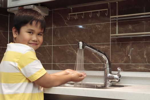 Child washing hands in sink in a modern kitchen.
