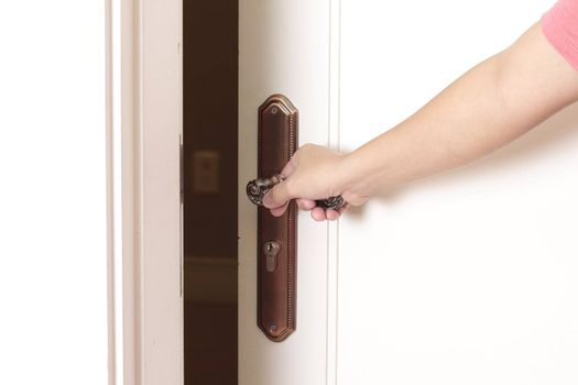 Opening the door with hand on the doorknob