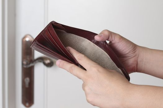 Empty wallet on a house wall background. Bankruptcy concept.