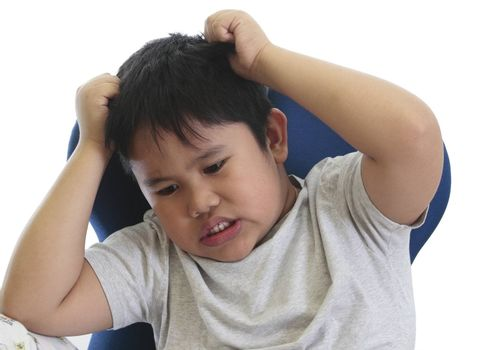 worried boy scratching his head in a white background