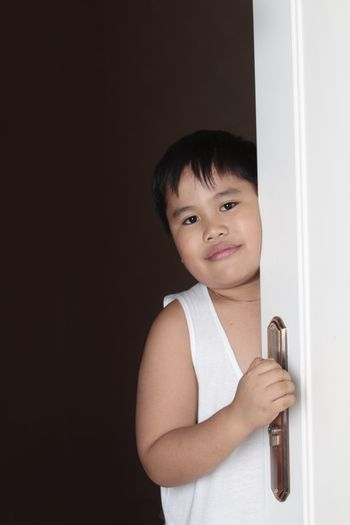 smiling happy asian boy looking throught the door