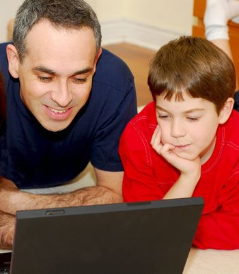 Father and son lying on the floor at home and looking into a portable computer