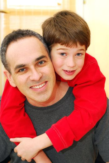 Portrait of smiling father and son inside