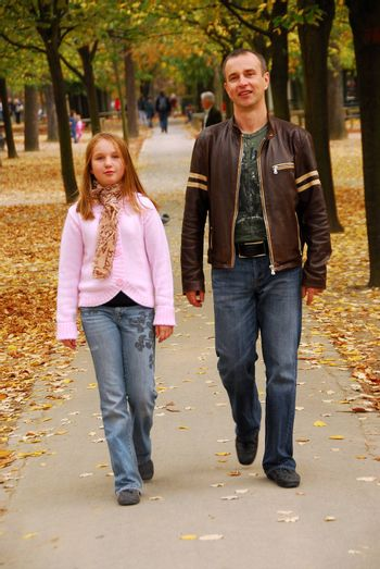 Father and daughter taking a walk in an autumn park