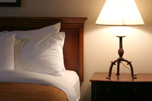 Comfortable and serene bedside lit by lamp light;