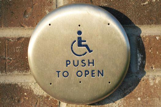 Handicap push to open button along exterior brick wall