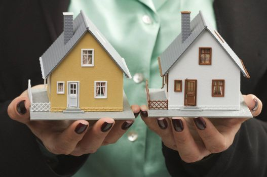 Female hands holding two houses.