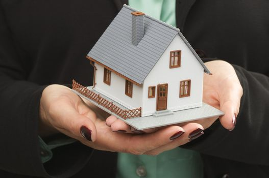 Female hands holding small house.