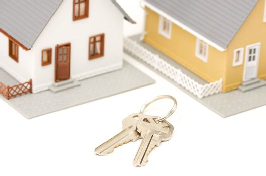 Keys and Houses isolated on a white background. Focus is on the keys.